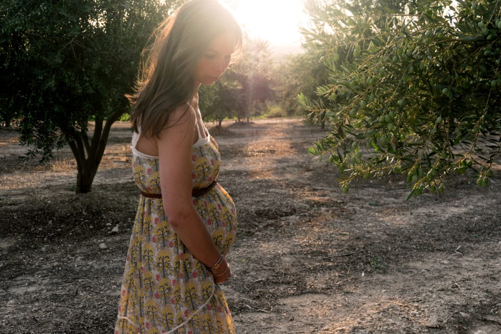 Pregnant woman looking pensively at the ground
