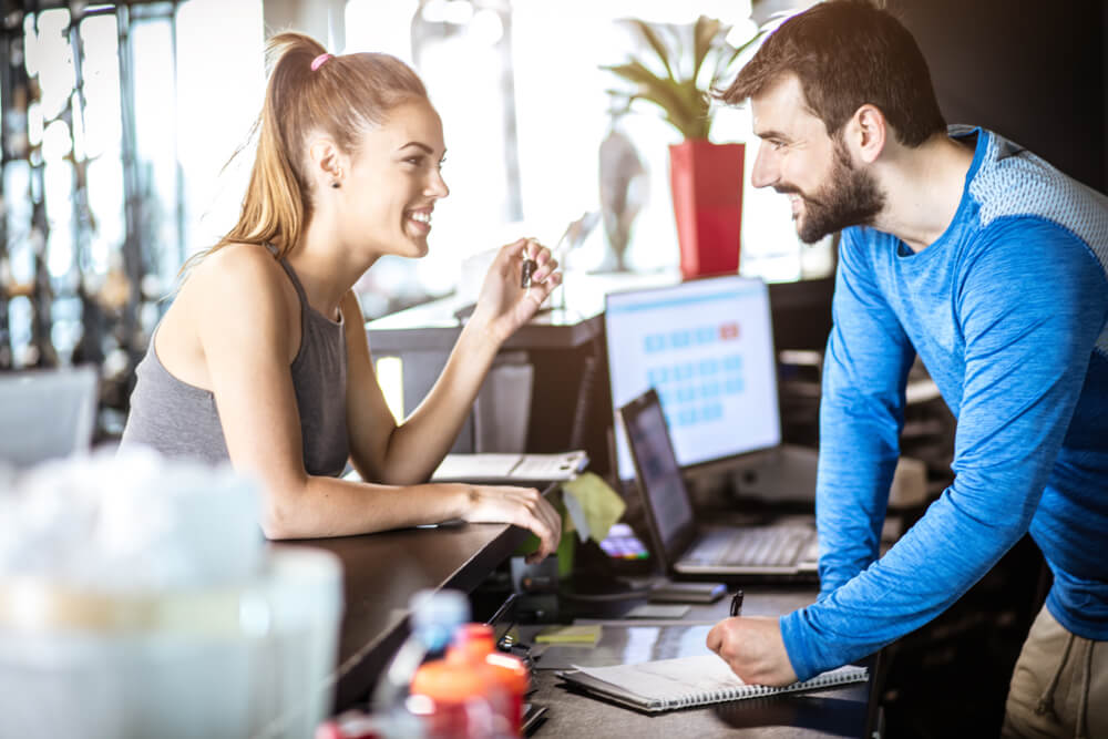 A young attractive woman leans over the reception desk at a gym, smiling at the gym manager on the other side who is marking something off his pad and smiling back at her as he does so. A happy client is a returning client.