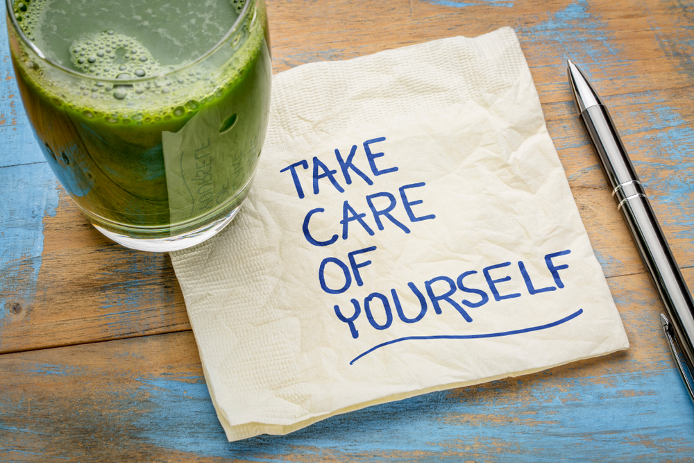 A glass filled with a green smoothie, rests on a napkin that has 'Take care of yourself' written on it